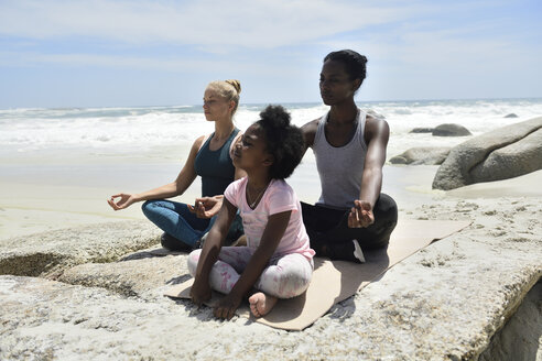 Mother with daughter and friend doing a yoga exercise on the beach - ECPF00394