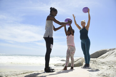 Mother with daughter and friend exercising with a ball on the beach - ECPF00400