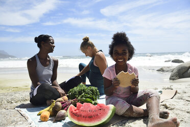 Mother with daughter and friend having a picnic on the beach - ECPF00424