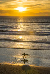 USA, California, Del Mar, female surfer at the beach at sunset - RUNF01136
