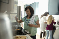 Latinx multi-generation women making pancakes in kitchen - HEROF19095