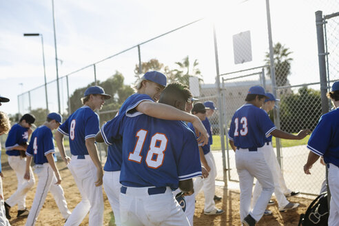 Happy baseball players hugging, walking off sunny field - HEROF19200