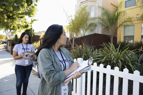 Latinx female volunteers with clipboards volunteering, canvassing voters door-to-door - HEROF19224