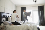 Playful father and son pillow fighting on bed - HEROF19293