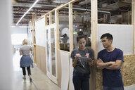 Engineers talking, using digital tablet in workshop corridor - HEROF19378