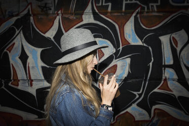 Blonde young woman in hat drinking iced coffee along graffiti wall - HEROF19417