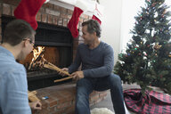 Father and son building a fire in fireplace in Christmas living room - HEROF19465