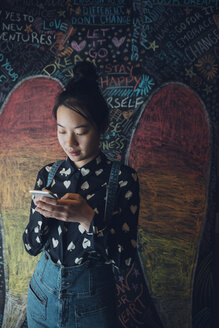 Asian tween girl texting with smart phone against wall with chalk angel wings - HEROF19480