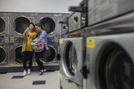 Smiling young women friends taking selfie, doing laundry at laundromat - HEROF19606