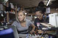 Female engineers using soldering iron on circuit board in workshop - HEROF19681