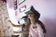 Girl sisters playing with virtual reality simulator glasses in bedroom - HEROF19726