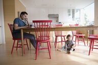 Father working at laptop at table with toddler daughter playing on floor - HEROF19729