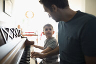 Father teaching toddler son playing piano - HEROF19732