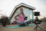 Female yoga instructor with digital tablet and video camera filming, vlogging on yoga mat on deck patio - HEROF19738