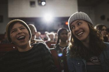 Laughing tween couple watching movie in dark movie theater - HEROF19783