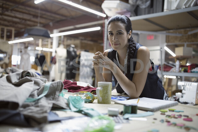 Portrait confident female fashion designer leaning on workbench in workshop - HEROF19819 - Hero Images/Westend61