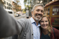 Personal perspective portrait smiling mature couple taking selfie on urban street - HEROF19843