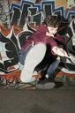 Portrait young man kicking against urban graffiti wall - HEROF19849