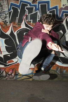 Portrait young man kicking against urban graffiti wall - HEROF19849
