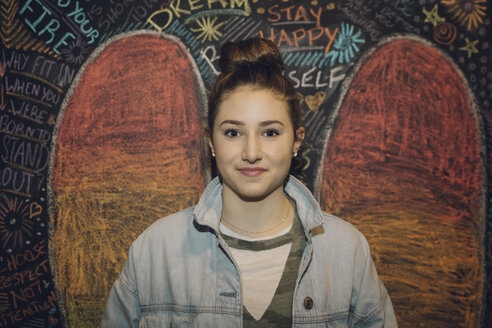 Portrait confident Caucasian tween girl with hair bun against wall with chalk wings - HEROF19891