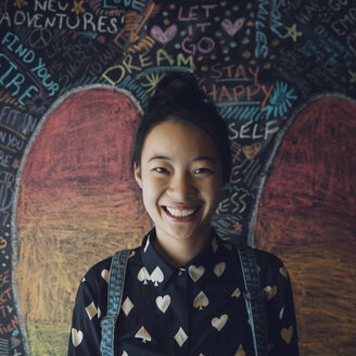 Portrait smiling, confident Asian tween girl against wall with chalk wings - HEROF19900