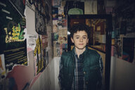 Portrait confident Caucasian tween boy in corridor with posters - HEROF19903