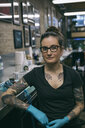 Portrait confident, determined tattoo artist in tattoo studio - HEROF19924
