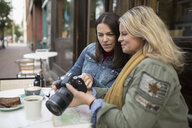 Mature women looking at digital camera viewfinder at sidewalk cafe - HEROF19963