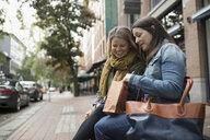 Mature women friends looking into shopping bag on urban sidewalk bench - HEROF19966