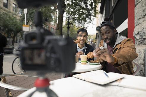 Men vlogging with video camera, eating at urban sidewalk cafe - HEROF19978