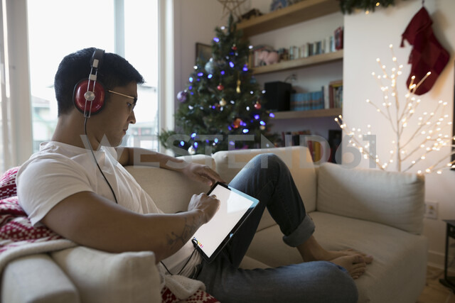 Man with headphones listening to music and using digital tablet on sofa in Christmas living room - HEROF20011 - Hero Images/Westend61