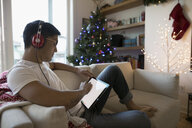 Man with headphones listening to music and using digital tablet on sofa in Christmas living room - HEROF20011