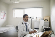 Male doctor working at laptop in doctor - HEROF20014