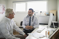 Male doctor talking with senior patient in doctor - HEROF20017