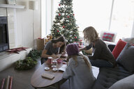 Mother and daughters making Christmas cards near Christmas tree in living room - HEROF20032