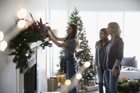 Mother and daughters decorating, hanging garland on fireplace mantle in living room - HEROF20038