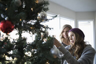 Mother and daughter decorating Christmas tree, hanging ornaments in living room - HEROF20044