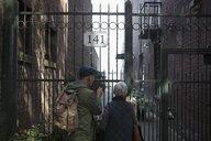 Senior couple looking at urban apartments beyond gate - HEROF20089