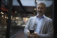 Senior man texting with smart phone on urban sidewalk - HEROF20101