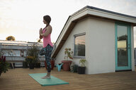 Serene woman standing in yoga tree pose with hands at heart center on yoga mat on deck patio - HEROF20104