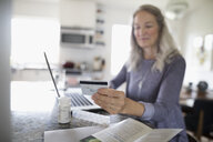 Senior woman with credit card reordering prescription medication at laptop in kitchen - HEROF20110