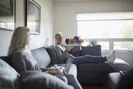 Senior couple relaxing, using laptop on living room sofa - HEROF20119