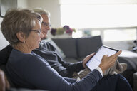 Senior couple using digital tablet on living room sofa - HEROF20134