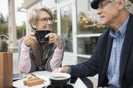 Senior couple talking and drinking coffee at sidewalk cafe - HEROF20146