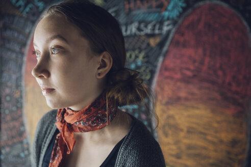 Serious, pensive Caucasian tween girl looking away against wall with chalk - HEROF20176