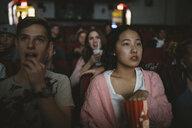Serious tween girl watching movie, eating popcorn in dark movie theater - HEROF20179