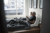 Senior couple relaxing, using digital tablet in bed in urban apartment - HEROF20200