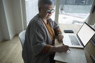 Senior woman working at laptop, sketching in notebook - HEROF20203