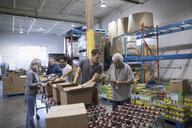 Volunteers boxing canned food for food drive in warehouse - HEROF20272
