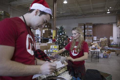 Volunteers in Santa hats sorting clothing for clothing drive in warehouse - HEROF20281
